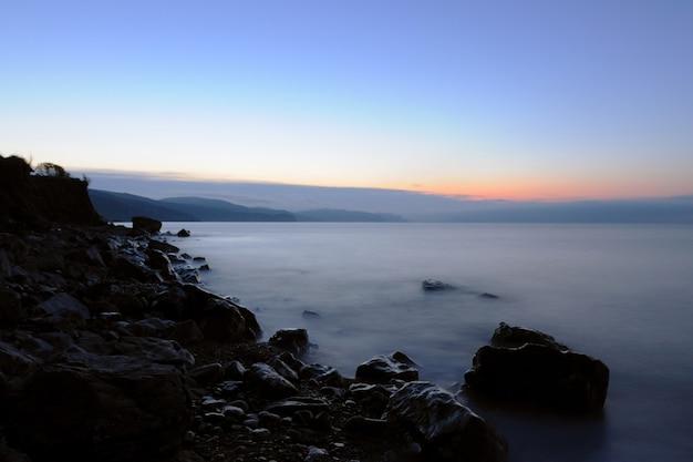 Beau paysage, coucher de soleil au bord de la mer, le soleil se lève derrière les montagnes, la plage est parsemée de pierres