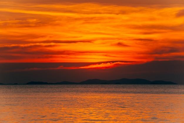 Beau paysage coucher de soleil flamboyant et ciel orange au-dessus, fond estival.