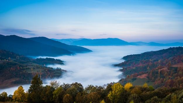 Beau paysage du matin avec des montagnes brumeuses d'automne.