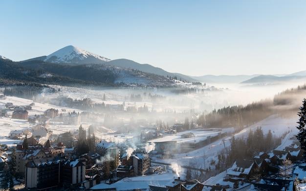Beau paysage du matin. les premières ombres du soleil levant sur les pentes des montagnes d'hiver dans une brume blanche et une station de ski