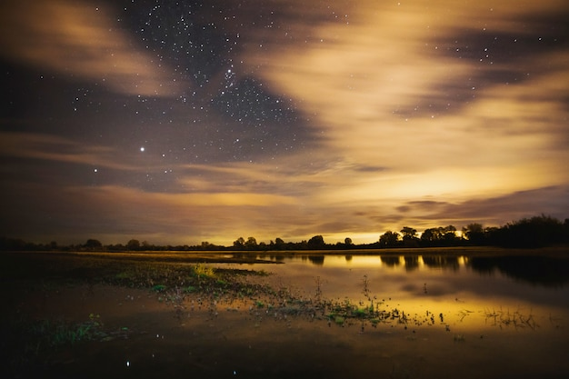 Beau paysage étoilé de nuit. les étoiles se reflètent dans l'eau. astrophotographie. ciel étoilé clair. vitesse d'obturation lente. le ciel spectaculaire.