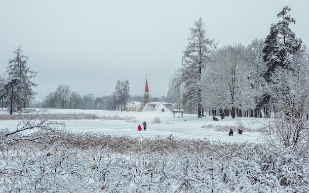 Beau paysage d'hiver avec un lac gelé et des arbres blancs dans le gel. pêcheur marchant sur un lac gelé. gatchina. russie.