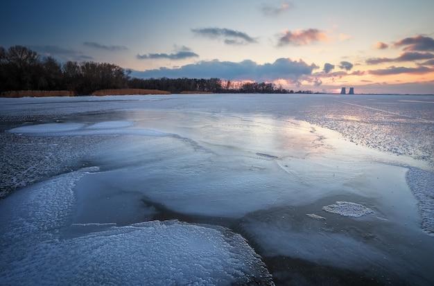 Beau paysage d'hiver avec réservoir gelé au coucher du soleil et centrale électrique.