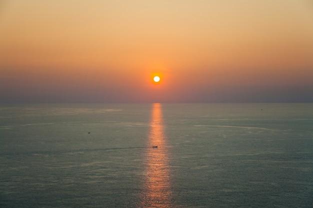 Beau paysage marin avec le coucher du soleil et un bateau dans les rayons