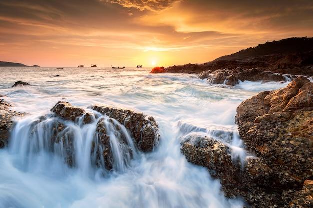 Beau paysage marin avec mer et rocher sur fond de coucher de soleil