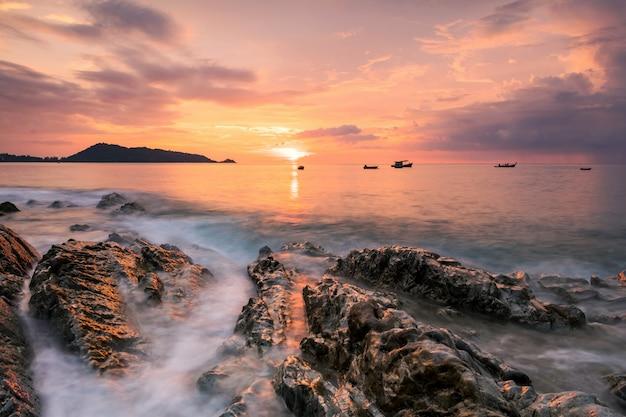 Beau paysage marin de mouvement à travers une arche en pierre naturelle au coucher du soleil avec un ciel crépusculaire à kalim près de la plage de patong, phuket, thaïlande. paysage marin au crépuscule. vacancier pour les vacances d'été dans un pays tropical.