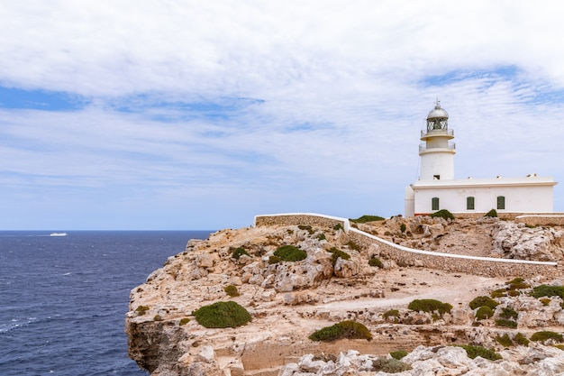 Beau paysage marin avec un phare sur une falaise et un bateau de croisière dans la mer. minorque, iles baléares, espagne