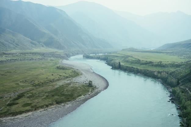 Beau paysage de montagne brumeux avec une large rivière de montagne. paysage sombre vert foncé avec grande rivière de montagne dans la brume. vue atmosphérique sombre sur la grande rivière parmi les grandes montagnes par temps de pluie.