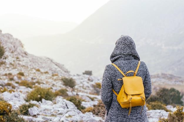 Beau paysage de montagne avec une jeune femme portant un sac à dos jaune à la recherche de la lumière du soleil