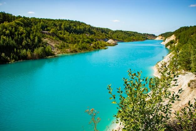 Beau paysage de montagne un lac avec de l'eau turquoise inhabituelle dans la carrière de cratère de craie en biélorussie journée d'été ensoleillée