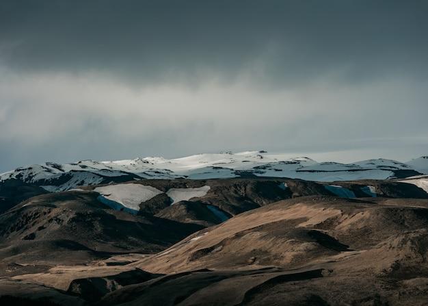 Beau paysage naturel avec des collines enneigées et un ciel gris foncé
