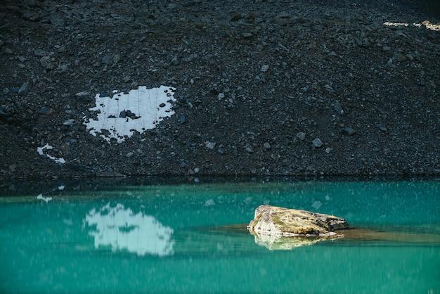 Beau paysage pittoresque avec rocher moussu dans le lac de montagne turquoise. lac glaciaire azur au soleil. paysages colorés avec de la pierre moussue au-dessus de la surface de l'eau claire. lac ensoleillé et montagne pierreuse.