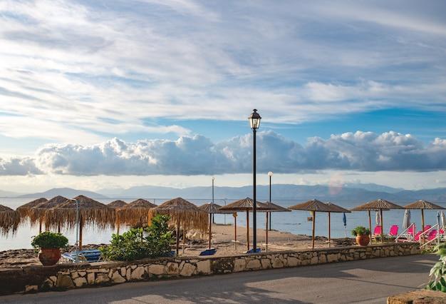 Beau paysage de la plage de la mer ionienne avec des chaises longues colorées et des parasols en staw