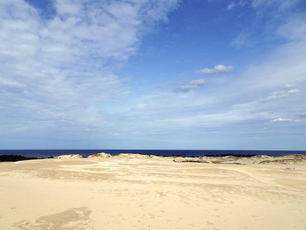 Beau paysage d'une plage de sable sous un ciel nuageux à leba, pologne