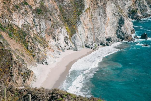 Beau paysage près de la ville de monterey en californie. océan turquoise avec de grosses vagues et des falaises rocheuses. paradise beach de californie. océan pacifique et falaises avec des plantes.