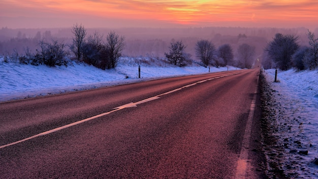 Beau paysage d'une route entourée d'arbres recouverts de neige au lever du soleil