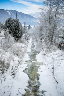 Beau paysage de ruisseau de montagne rapide à la forêt couverte de neige