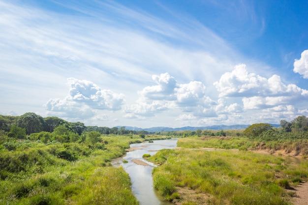 Beau paysage avec terrain gazonné, petite rivière, le fond et le ciel