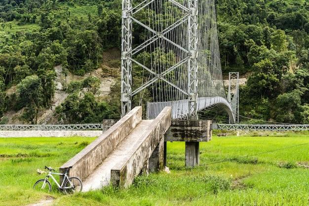 Beau paysage avec vélo blanc garé au pont suspendu pour piétons
