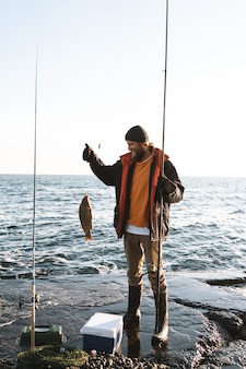 Beau pêcheur barbu brutal portant un manteau debout avec une canne à pêche au bord de la mer, montrant des poissons pêchés