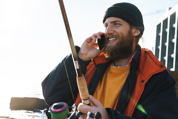Beau pêcheur barbu brutal portant un manteau debout avec une canne à pêche au bord de la mer, utilisant un téléphone portable, parlant