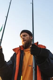 Beau pêcheur barbu brutal portant un manteau debout avec une canne à pêche au bord de la mer
