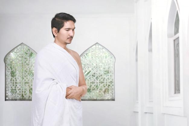 Beau pèlerin musulman asiatique priant