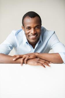 Beau penché sur l'espace de copie. bel homme africain en chemise bleue se penchant sur l'espace de copie et souriant en se tenant debout sur fond gris