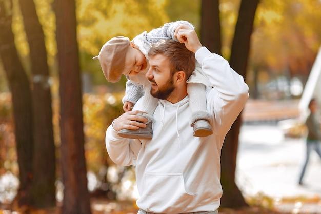 Beau père dans un pull gris, jouant avec une petite fille dans un parc en automne