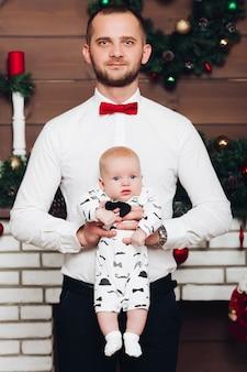Beau père heureux en chemise blanche et cravate tenant petit fils à la main