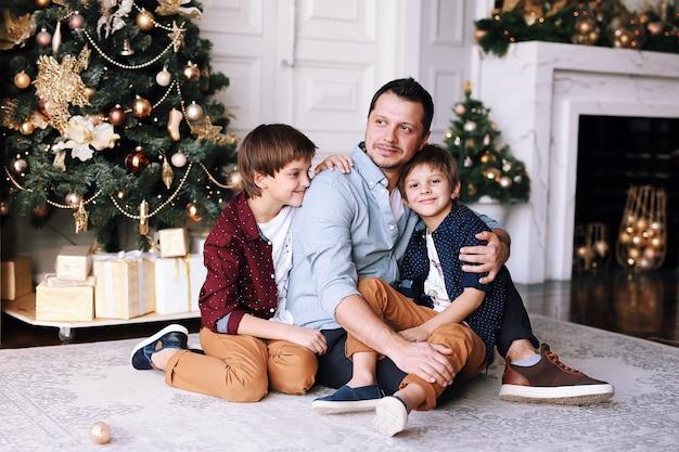 Beau père jouant avec ses drôles de fils à côté de l'arbre de noël à la maison