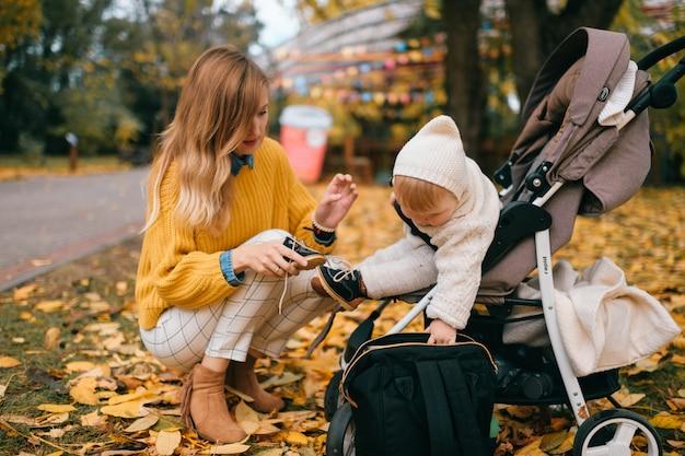 Un beau petit bébé dans une poussette à l'extérieur à l'automne avec une belle maman heureuse.