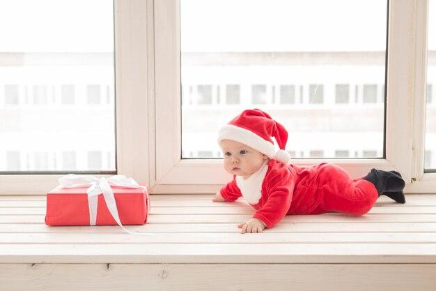 Beau petit bébé fête noël. les vacances du nouvel an. bébé en costume de noël et en bonnet de noel.