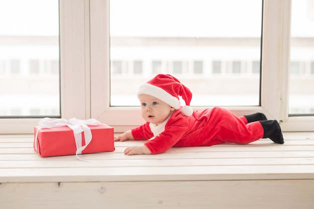Beau Petit Bébé Fête Noël. Les Vacances Du Nouvel An. Bébé En Costume De Noël Et En Bonnet De Noel. Photo Premium
