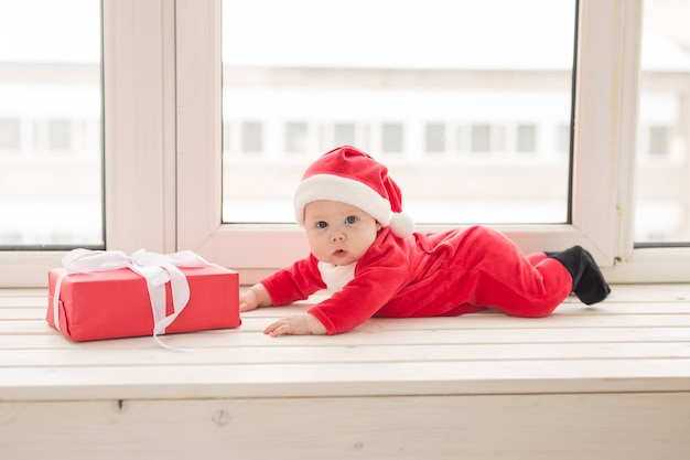 Beau Petit Bébé Fête Noël. Les Vacances Du Nouvel An. Bébé Curieux Dans Un Costume De Noël Et En Bonnet De Noel. Photo Premium