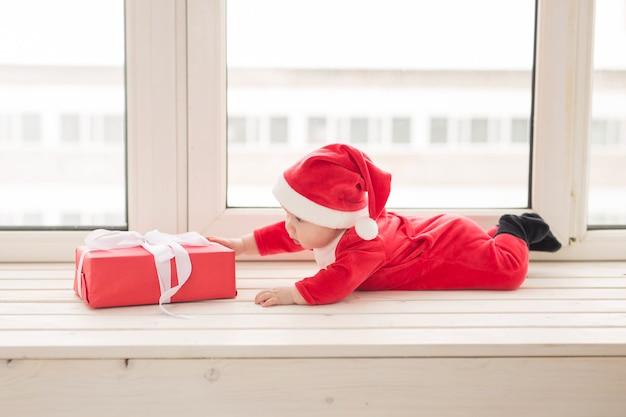 Beau petit bébé fête noël. les vacances du nouvel an. bébé curieux dans un costume de noël et en bonnet de noel.
