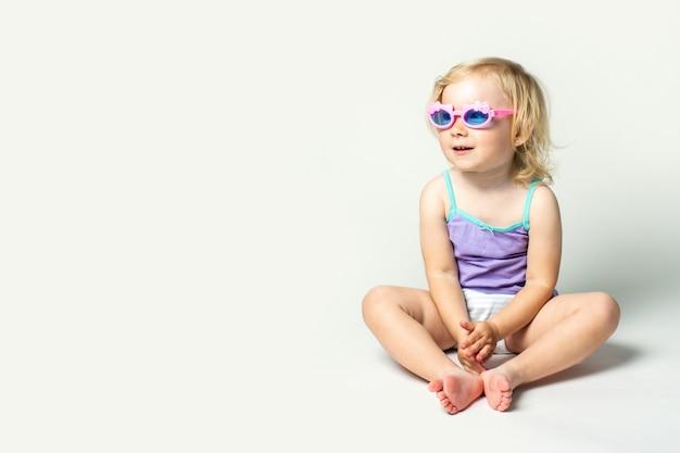 Beau petit bébé mignon est assis dans des lunettes de soleil