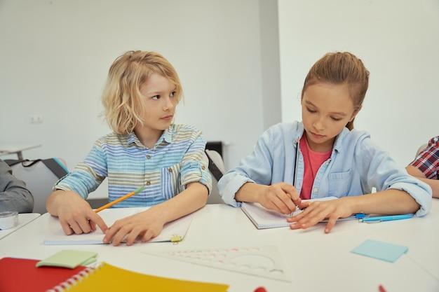 Beau petit écolier et écolière étudiant et prenant des notes assis ensemble à la table