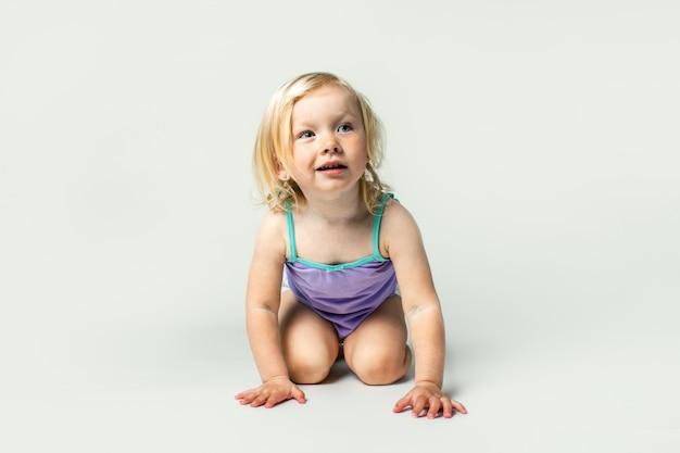 Beau petit enfant aux cheveux blonds souriant assis
