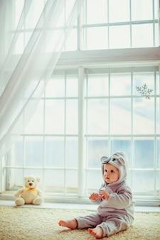 Beau petit garçon assis près de la fenêtre