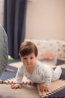 Beau petit garçon aux cheveux noirs dans le pyjama lumineux apprenant à ramper et à s'allonger sur le ventre sur le sol dans la pépinière