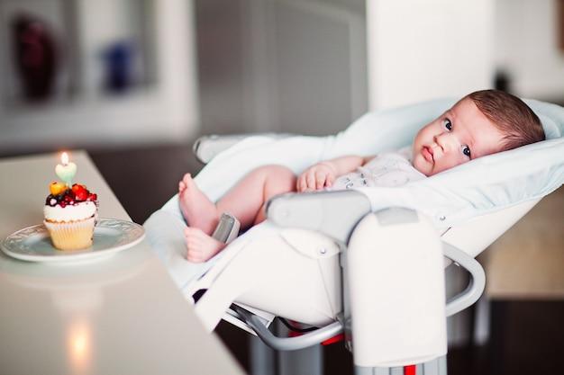 Un beau petit garçon aux yeux bleus dans une chaise haute, un petit gâteau avec une bougie sur la table. photo de haute qualité