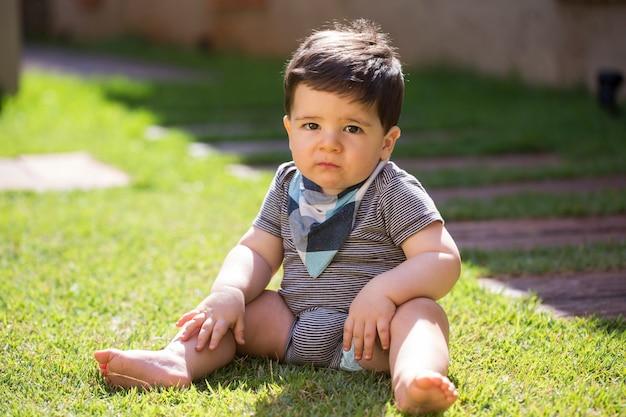 Beau petit garçon brésilien dans l'herbe en regardant la caméra. bébé sérieux.