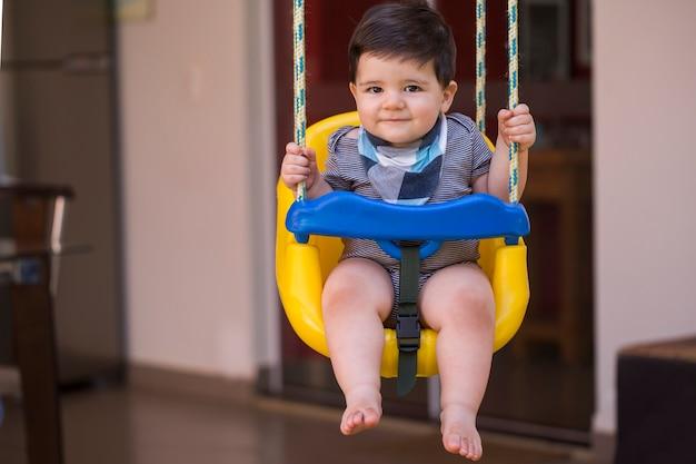 Beau petit garçon brésilien regardant la caméra. bébé sur la balançoire. bébé heureux.