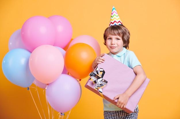Beau petit garçon en chapeau d'anniversaire posant avec grande boîte bleue et ballons colorés sur mur jaune