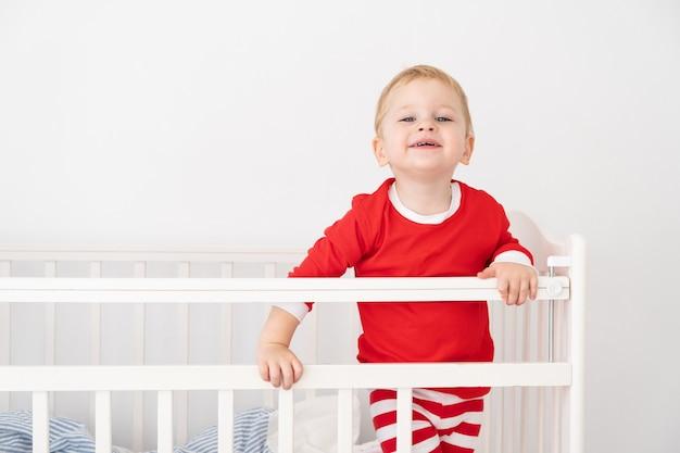 Beau petit garçon en costume rouge de noël souriant dans un lit bébé à la maison.
