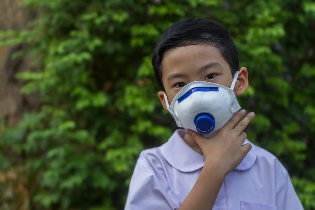 Beau petit garçon dans le bonheur uniforme de la maternelle à porter le masque anti-poussière. cheveux noirs asiatiques enfant de 6 ans portant un masque de protection blanc surdimensionné avec fond naturel vert flou.