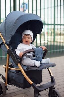 Un beau petit garçon dans un bonnet blanc est assis dans un landau, sourit et se plisse le nez