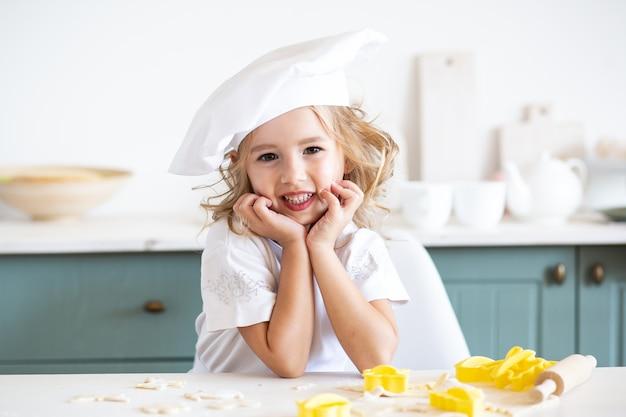 Beau petit garçon drôle, préparez des biscuits dans la cuisine domestique