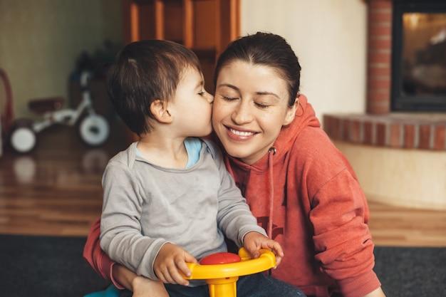 Beau petit garçon embrassant sa mère avec des taches de rousseur tout en jouant avec une voiture restant à la maison en quarantaine